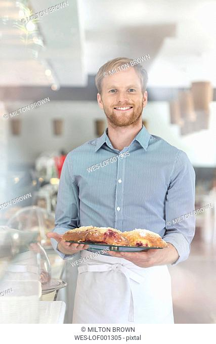Smiling waiter in a cafe serving pastries