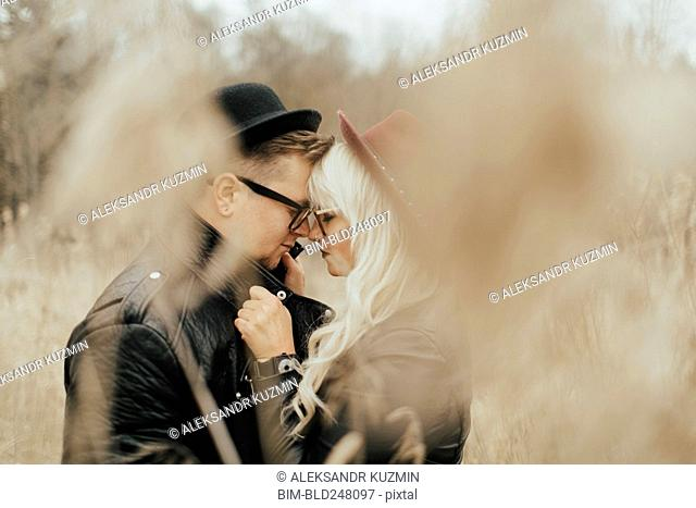 Middle Eastern couple rubbing noses in field
