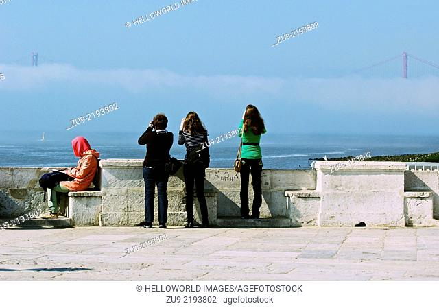 A woman sits reading by the river Tejo while 3 tourists take photos of the April 25th bridge in the mist, Lisbon, Portugal, western Europe