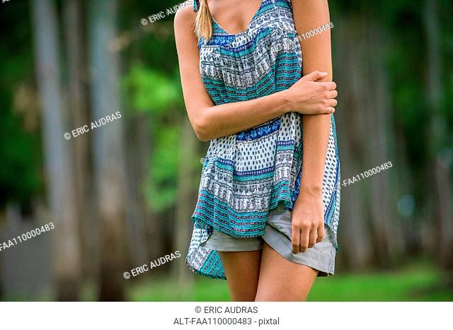 Young woman standing with arm folded across stomach, cropped