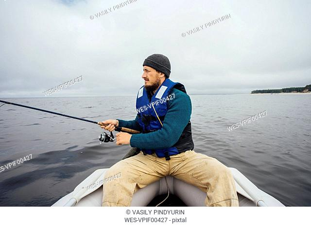 Man sitting on boat fishing with fishing rod