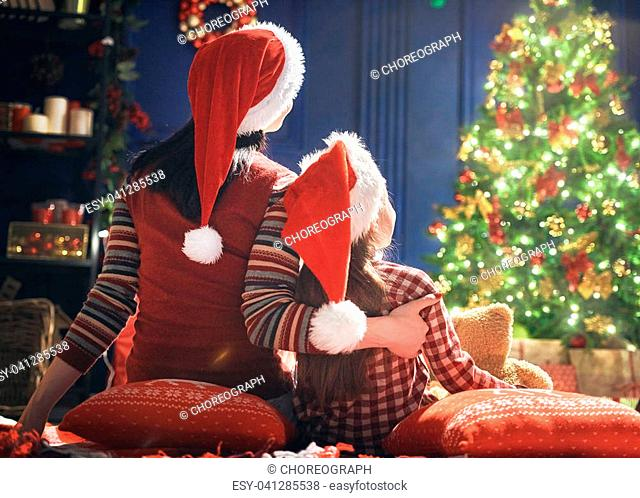 Merry Christmas and Happy Holidays! Cheerful mom and her cute daughter girl at home. Parent and little child looking at tree indoors