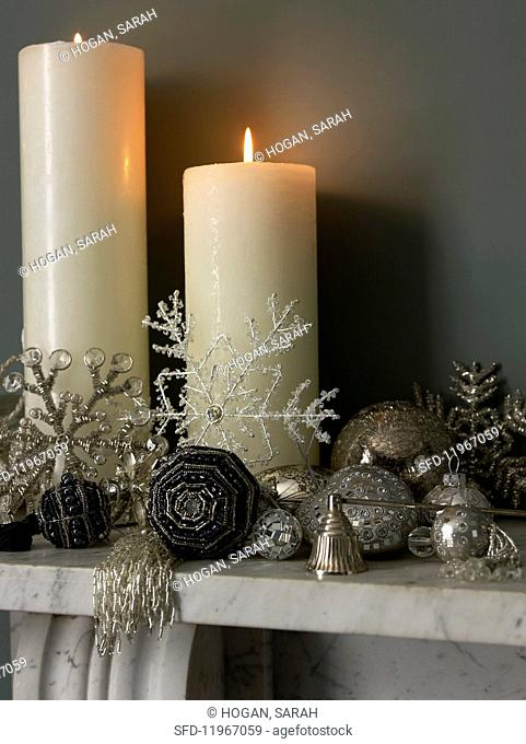 Burning white pillar candles and silver Christmas decorations on a mantelpiece