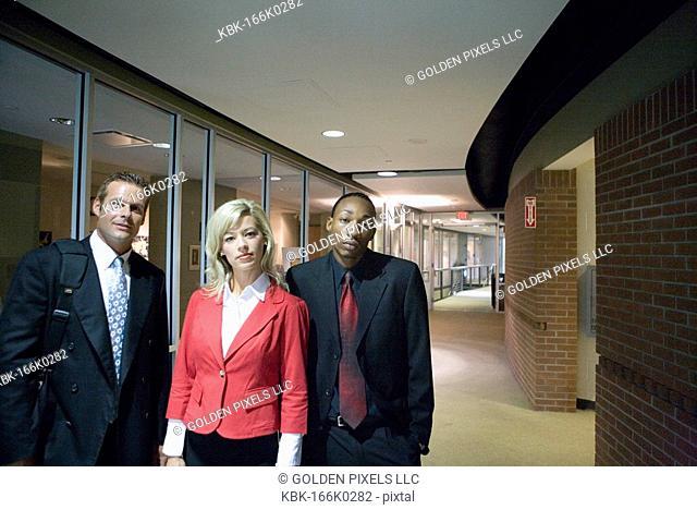 Portrait of business people standing in office hallway