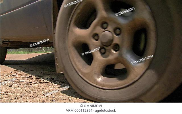 Close up of wheels of blue VW van as its pulls away on dirt track with trees and sign post behind