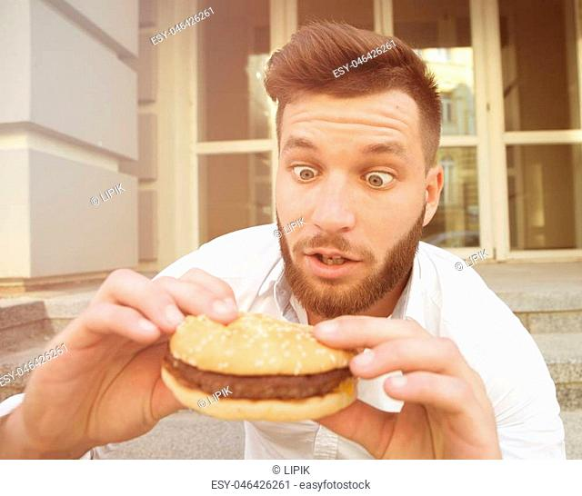 Handsome young man dreaming of tasting delicious cheeseburger very much. Surprised man looking at it with excitement. Toned image
