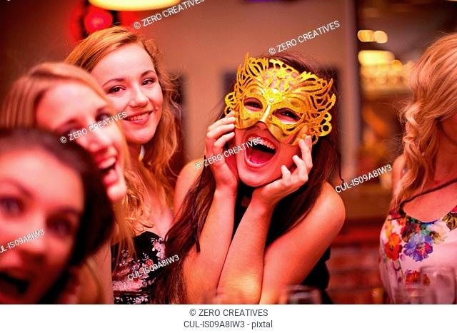 Young woman wearing masquerade mask at hen party