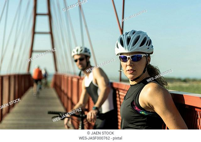 Sportive man and woman with bicycles resting on a bridge