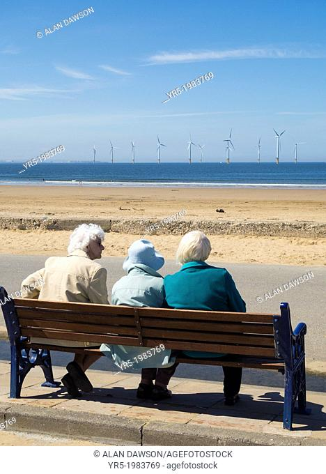Three elderly ladies sitting on bench near the beach with offshore windfarm in distance. Redcar, north east England, United Kingdom