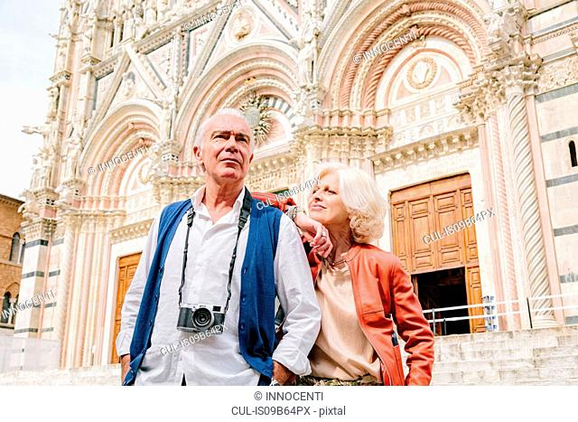Tourist couple in front of Siena cathedral, Tuscany, Italy