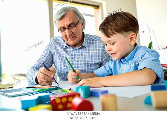 Grandfather drawing with grandson