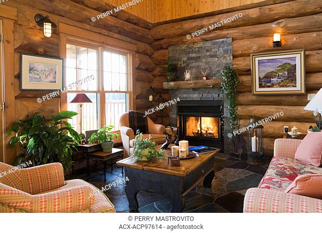 Upholstered chairs, sofa and wooden coffee table with lit fireplace in the living room inside a handcrafted spruce log home, Quebec, Canada