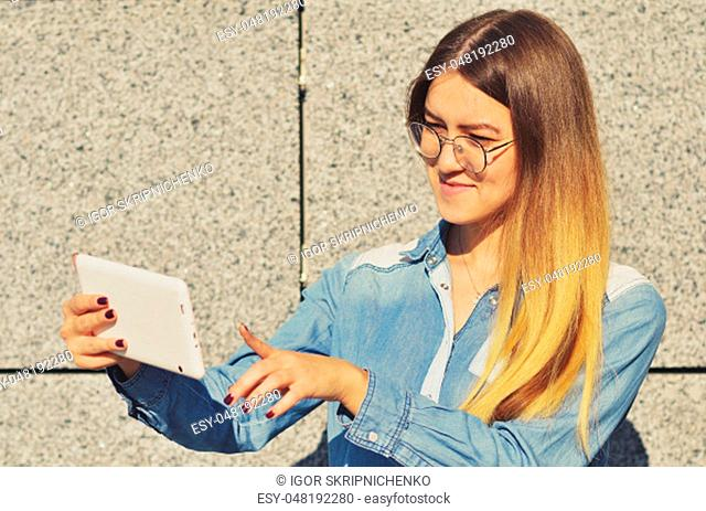 A young girl with glasses who is wearing a denim shirt, holding a tablet in her hand and clicks on the screen, horizontal photo
