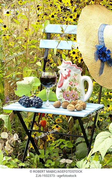 Summer arrangements in the garden includes blue painted chair, glass of domestic Slovenian vine, grapes, straw hat, walnuts and pitcher