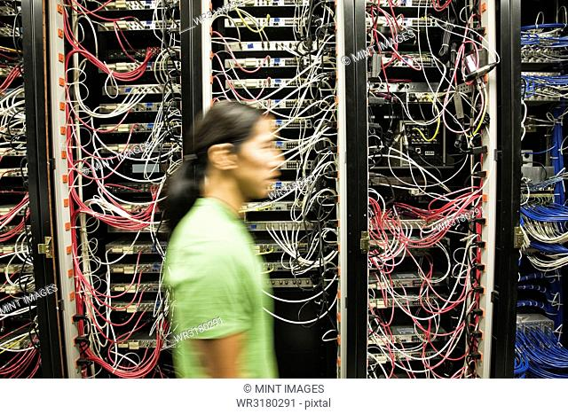 Asian American male technician working on a CAT 5 cable bundling system in a large computer server room