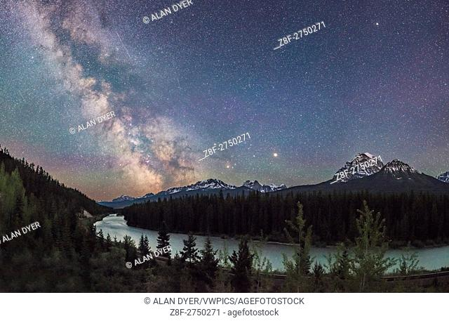 The Milky Way, often described in mythologies as a river in the sky, shines over the Bow River in Banff National Park on a very clear night in early June