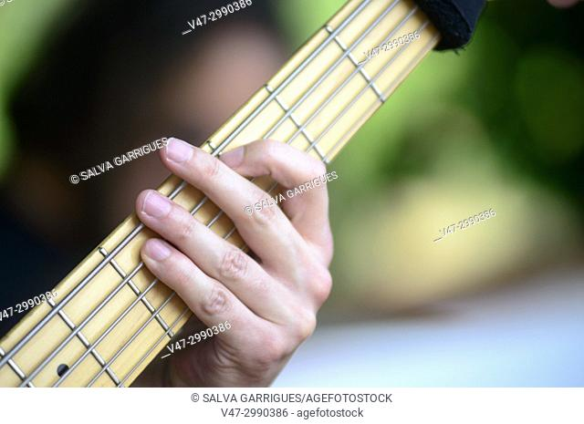 Close-up of guitar and guitarist's hands at an outdoor concert