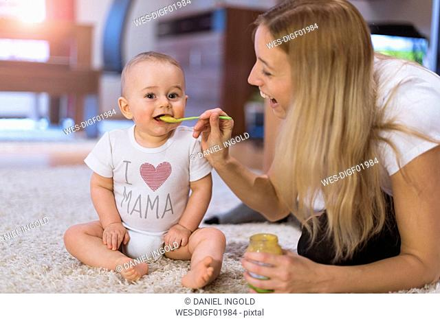 Mother feeding her baby son at home