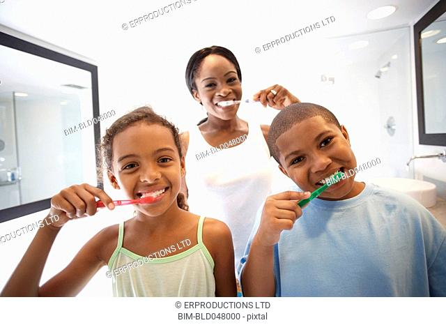 African American mother and children brushing teeth