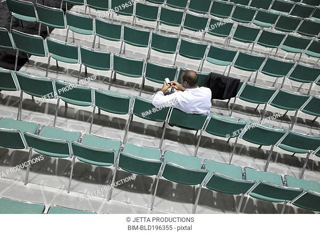 Black businessman text messaging in empty conference center