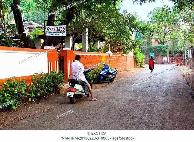 Man parking a scooter outside the hotel building, Basilico Italian Restaurant, D'Mello Vaddo, Anjuna, Bardez, North Goa, Goa, India