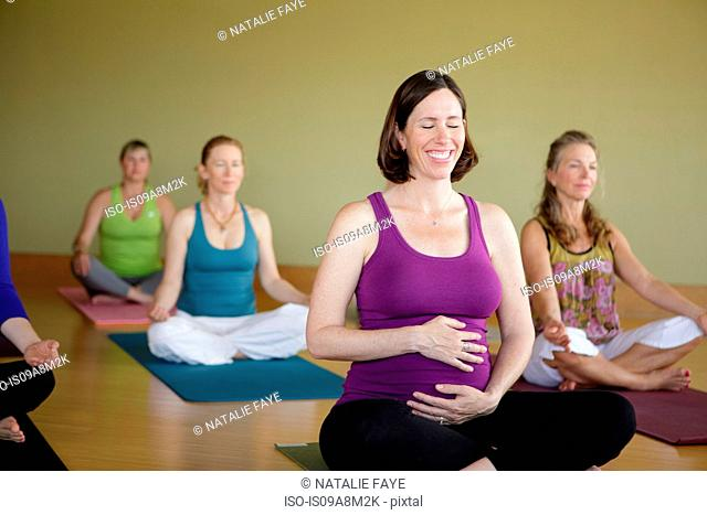 Pregnant woman in yoga class smiling and holding her stomach