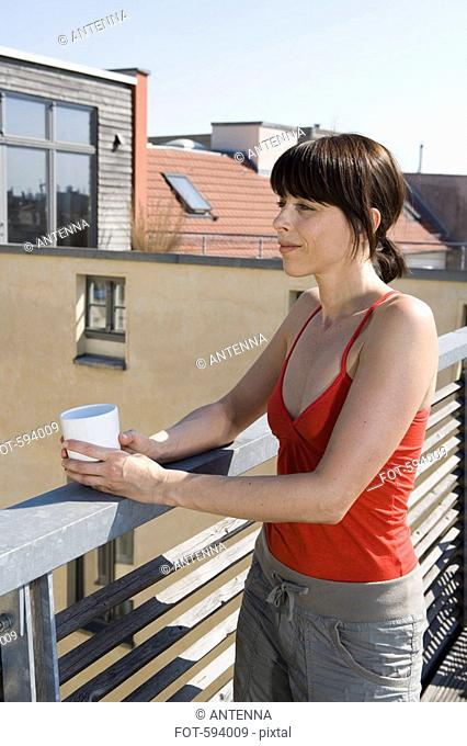 A woman standing on a rooftop terrace with a cup