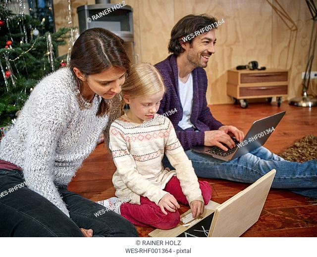 Father using laptop, mother playing with daughter on toy computer on Christmas Eve