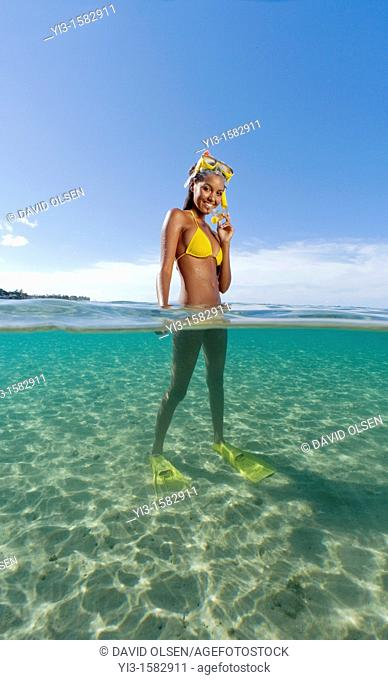 Over and underwater view of smiling girl with snorkel, mask, and fins at Lahaina, Maui, Hawaii