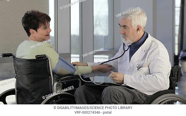Doctor with Muscular Dystrophy in wheelchair taking a patient's blood pressure