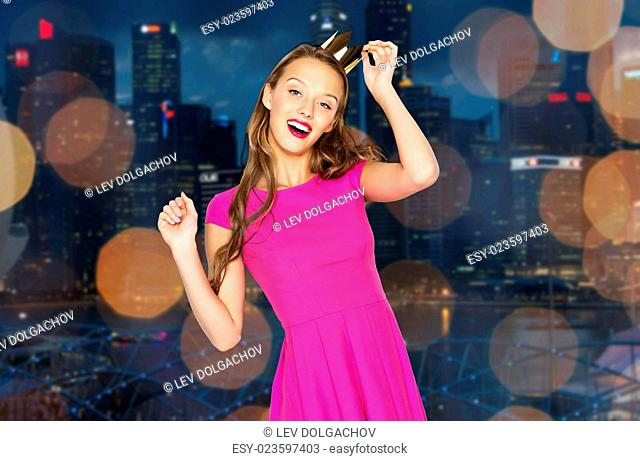 people, holidays, party and night life concept - happy young woman or teen girl in pink dress and princess crown dancing over night singapore city lights...