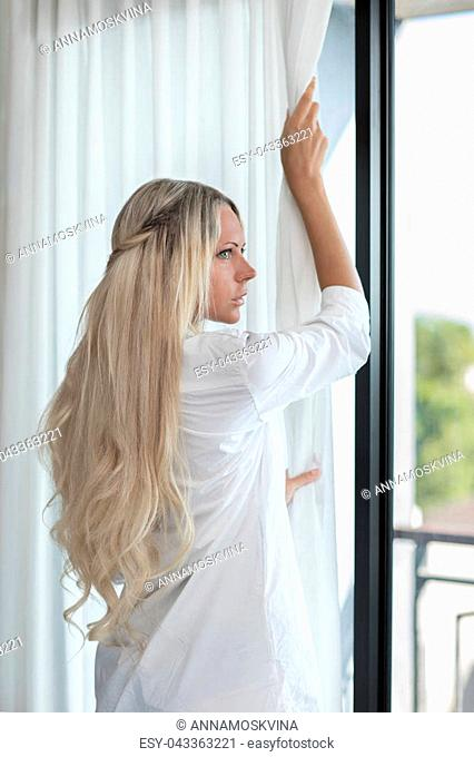Young blonde slim woman with long hair opens white curtains after wake up after sleep