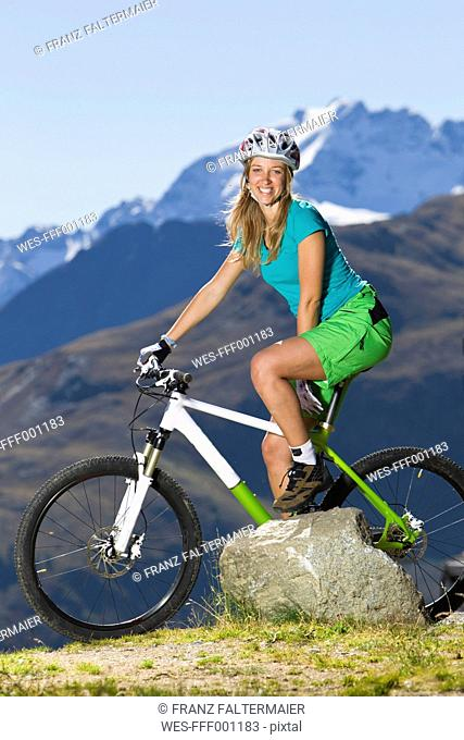 Italy, Livigno, View of woman sitting on mountain bike