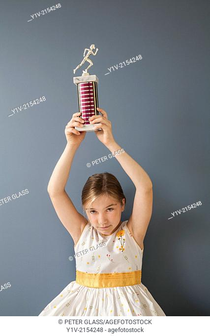 Preteen blond girl holding a trophy