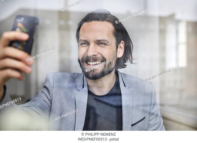 Portrait of laughing man behind windowpane taking selfie with cell phone