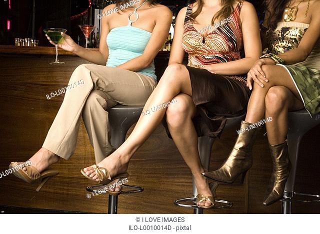 Three young women sitting at a bar
