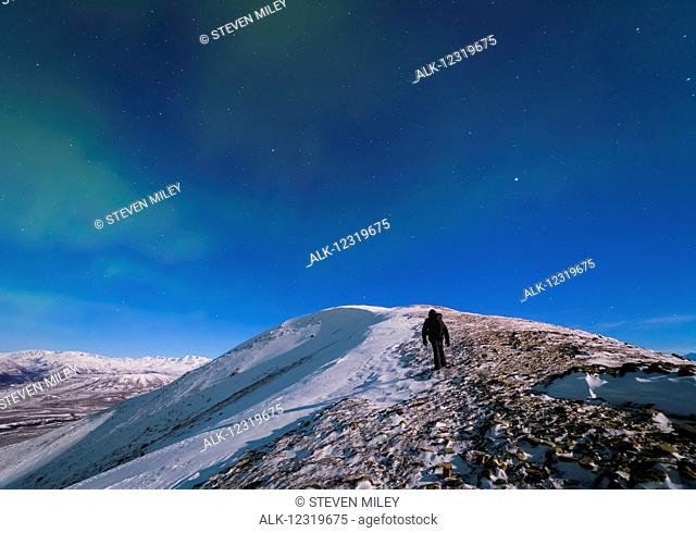 A man climbs to the top of Donnelly Dome (near Delta Junction) on a moonlit night in subzero temperatures to photograph the aurora borealis