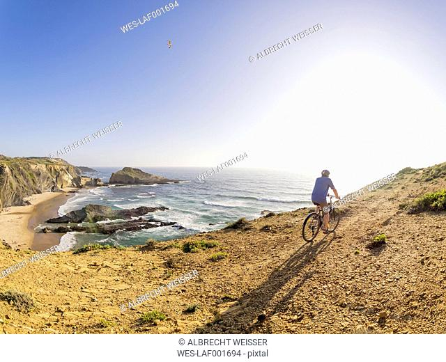 Portugal, Senior man mountain biking at the sea