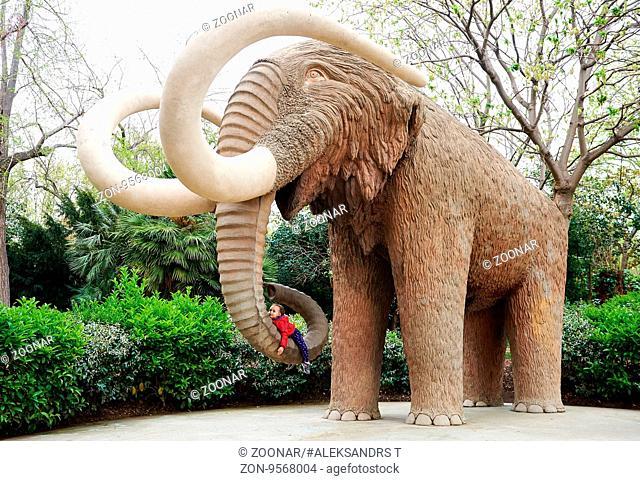 Little girl lying on an elephant's proboscis. Elephant statue in the Parc de la Ciutadella in Barcelona, Spain