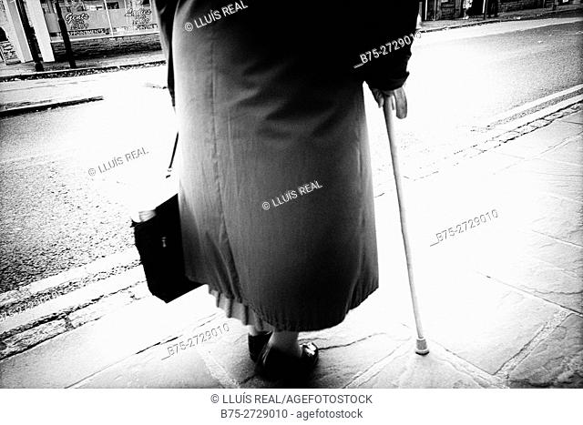 Unrecognizable old lady with coat and bag in hand, walking down the street with a cane, rear view. East End, London, England, UK