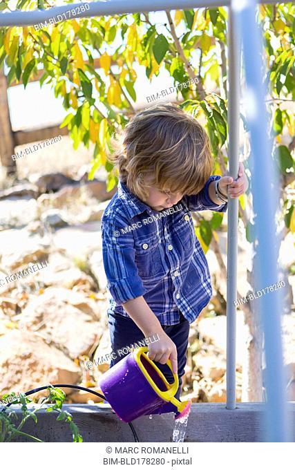 Caucasian boy watering plants in backyard