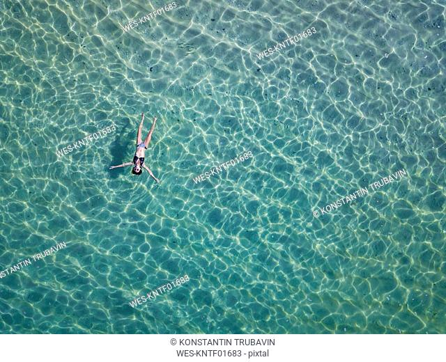 Indonesia, Bali, Melasti, Aerial view of Karma Kandara beach, woman floating on water