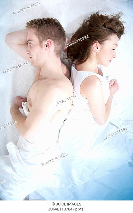 Young couple lying back to back in bed