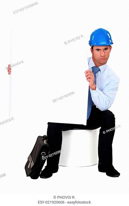 businessman with a helmet on his head holding a blank poster