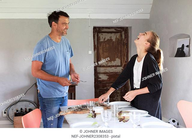 Father with teenage girl setting table