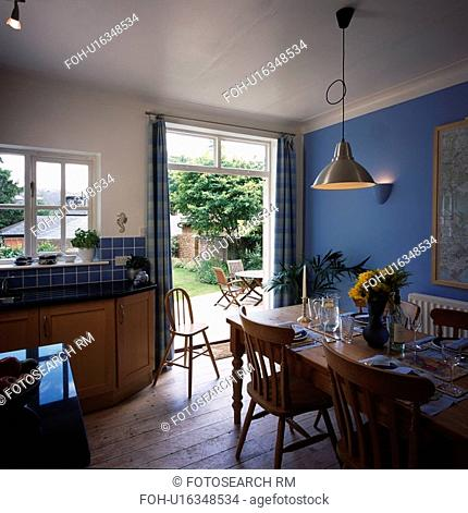 Pendant light above pine table and chairs in blue kitchen with wooden flooring and doors open to garden