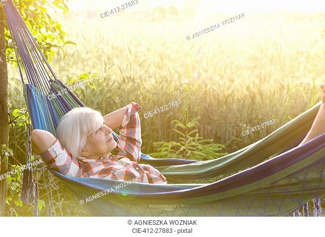 Serene senior woman laying in hammock next to rural wheat field