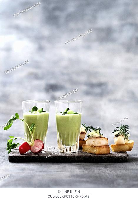 Glass of pea soup and scallop canapes