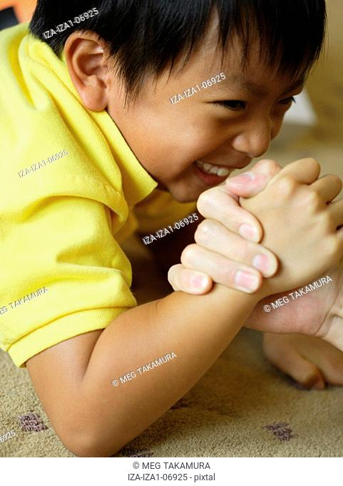 Side profile of a boy with his father arm wrestling