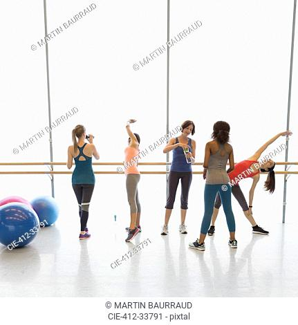 Women stretching and drinking water in exercise class gym studio